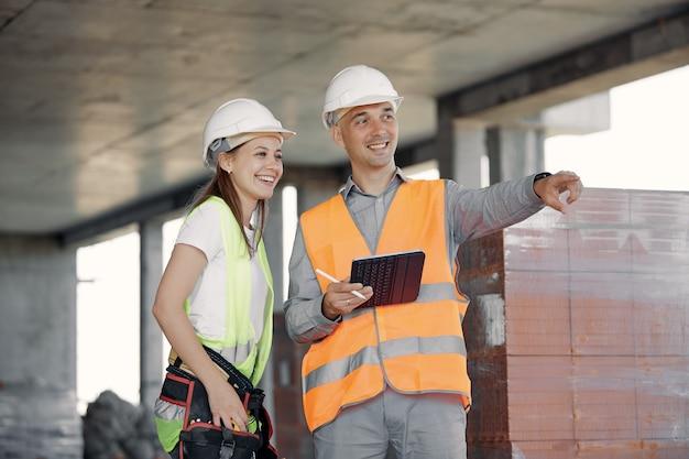 Inżynier z branży budowlanej omawia z pracownikiem plan budowy. wesołych i uśmiechniętych konstruktorów pracujących razem nad projektem