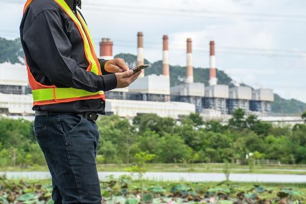 Inżynier z elektrownią węglową w tle.