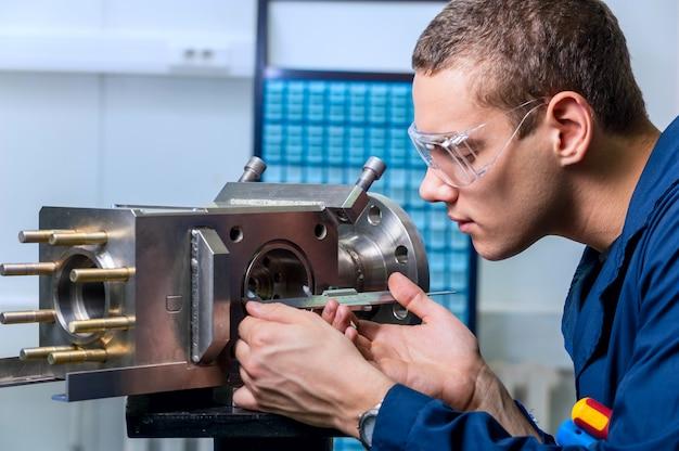 Inżynier z przyrządem pomiarowym suwmiarki w nowoczesnym laboratorium
