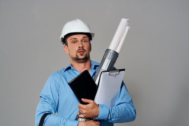 Inżynier z rysunkami w dłoni gest jasny tło