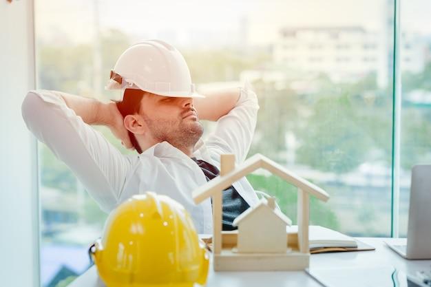 Inżynier zmęczony i drzemiący lub śpiący w biurze, gdy przerwa na lunch czas po ciężkiej pracy w nocy