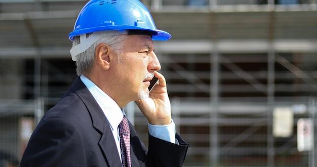 Inżyniera budowniczy opowiada na telefonie przy budową