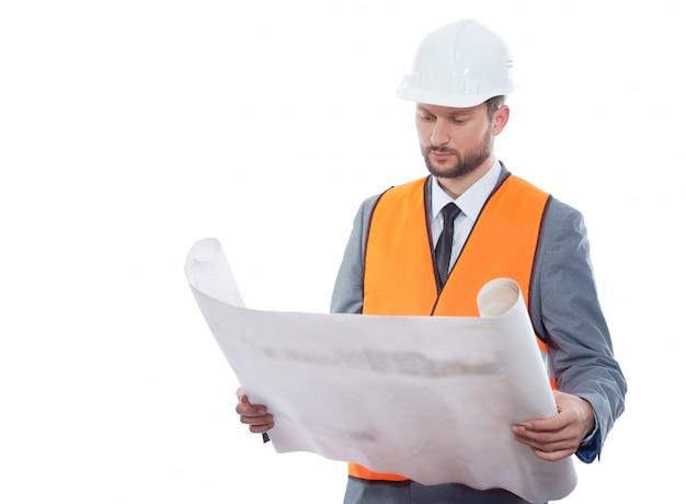 Inżyniera mienia projekty pozuje na białym tle jest ubranym ochronnego hełm i zbawczą kamizelkę.