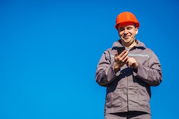 Inżyniera ochronnego hełma stojak na niebieskim niebie