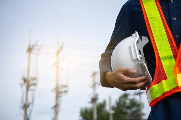 Inżynieria posiada białe czapki ochronne i tło słup elektryczny