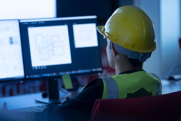 Inżynieria przemysłowa pracuje przed ekranem monitorującym w biurze centrum sterowania