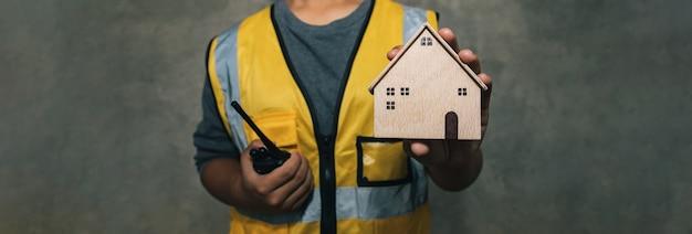 Inżynieria trzymająca drewniany nowoczesny dom do naprawy i renowacji nieruchomości ubezpieczenie domu użyj na stronie internetowej z banerem opieka nad obsługą klienta
