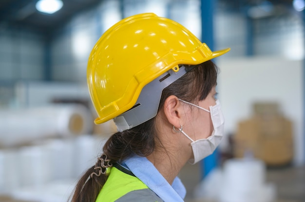 Inżynierka nosząca maskę medyczną, hełm ochronny pracujący w fabryce magazynowej