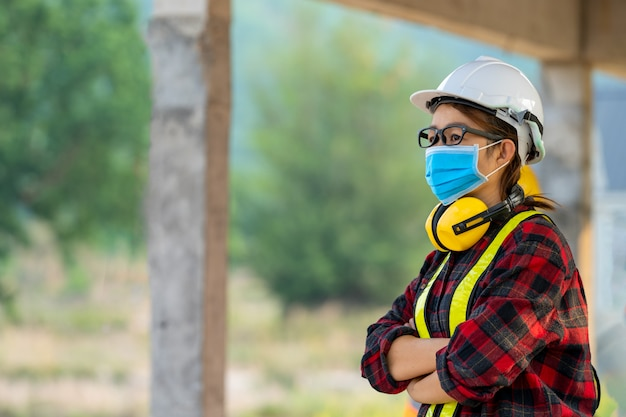 Inżynierka nosząca maskę ochronną w celu ochrony przed covid-19 z hełmem na placu budowy