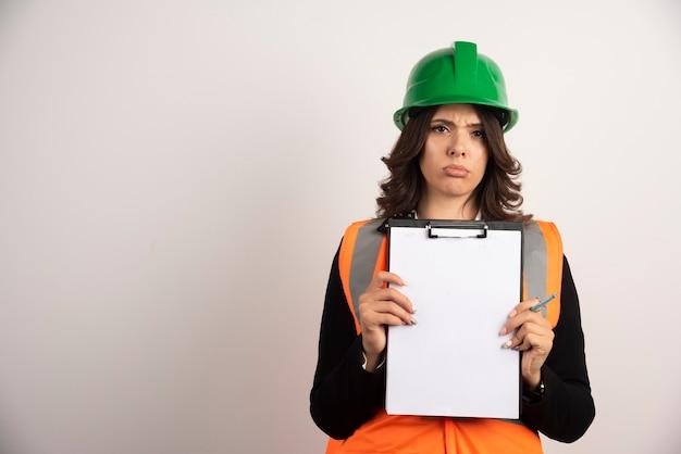 Inżynierka pokazująca ważne dokumenty ze smutną miną