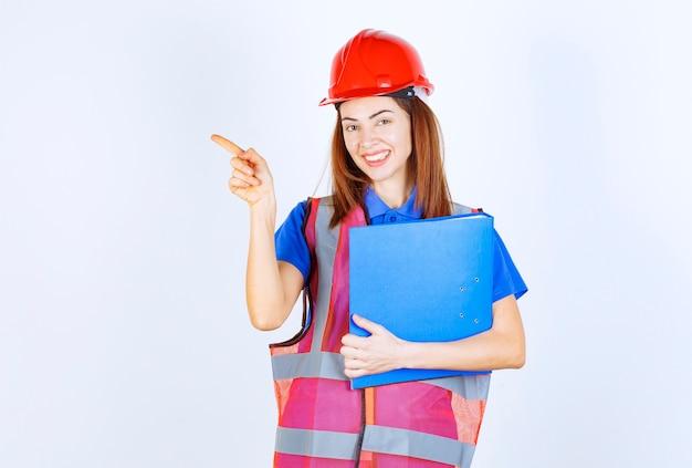 Inżynierka w czerwonym hełmie trzymająca niebieski folder projektu i przedstawiająca kogoś lub coś.