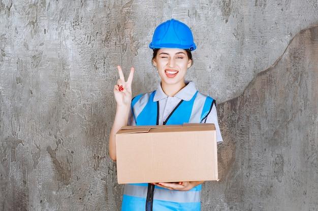 Inżynierka w niebieskim mundurze i hełmie, trzymająca kartonową paczkę i pokazująca pozytywny znak ręki.