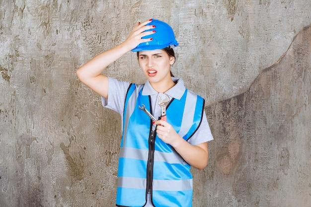 Inżynierka w niebieskim mundurze i hełmie trzymająca metalowy klucz i czująca się zagubiona i zamyślona, jak go używać.