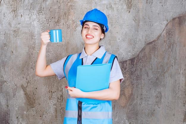 Inżynierka w niebieskim mundurze i hełmie, trzymająca niebieską filiżankę herbaty i niebieski folder z raportami