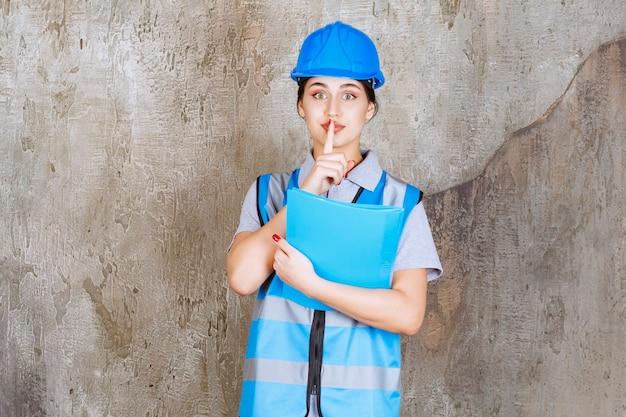 Inżynierka w niebieskim mundurze i hełmie trzymająca niebieską teczkę z raportami i proszącą o ciszę.