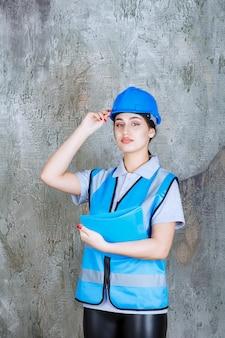 Inżynierka w niebieskim mundurze i hełmie, trzymająca niebieski folder z raportami
