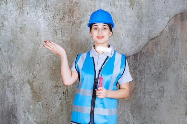 Inżynierka w niebieskim mundurze i hełmie, trzymająca rolkę do malowania i wskazującą na betonową ścianę z tyłu.