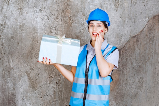 Inżynierka w niebieskim mundurze i kasku, trzymająca niebieskie pudełko upominkowe i wygląda na zaskoczoną i podekscytowaną