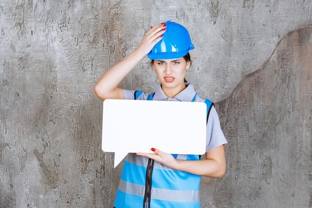 Inżynierka w niebieskim mundurze i kasku, trzymająca tablicę informacyjną z pustym prostokątem i wygląda na zdezorientowaną i przerażoną