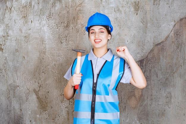 Inżynierka w niebieskim stroju i hełmie, trzymająca siekierę z drewnianą rączką i pokazująca pięść