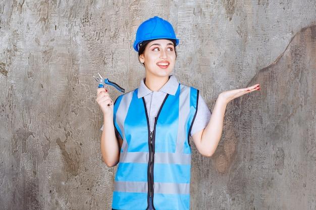 Inżynierka w niebieskim stroju i kasku trzymająca szczypce do prac naprawczych i wskazująca na betonową ścianę