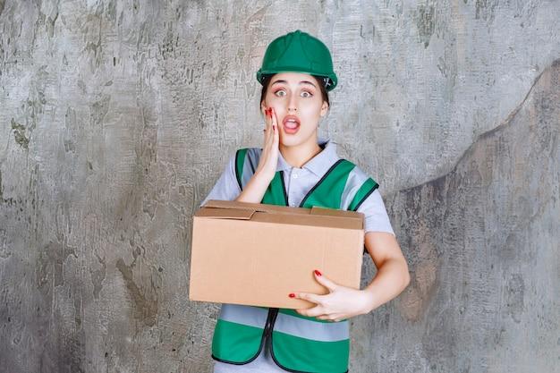 Inżynierka w zielonym hełmie trzymająca karton i wygląda na zdezorientowaną i przerażoną.