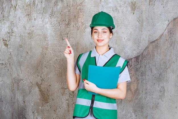 Inżynierka w zielonym hełmie trzymająca niebieską teczkę i wskazująca na kogoś dookoła