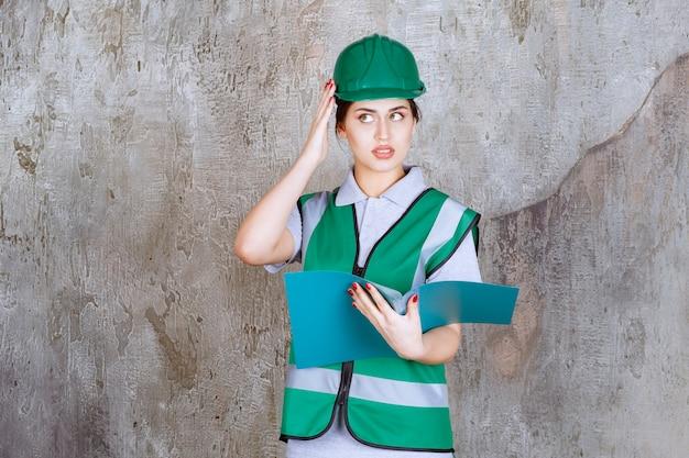 Inżynierka w zielonym hełmie trzymająca niebieski folder i wygląda na zdezorientowaną i zamyśloną