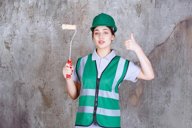 Inżynierka w zielonym kasku trzymająca rolkę do malowania ścian i pokazująca pozytywny znak ręki