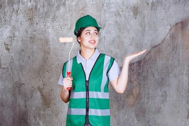 Inżynierka w zielonym kasku trzymająca rolkę do malowania ścian i wskazująca na swoją pracę
