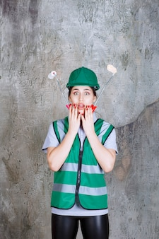 Inżynierka w zielonym kasku trzymająca rolkę do malowania ścian
