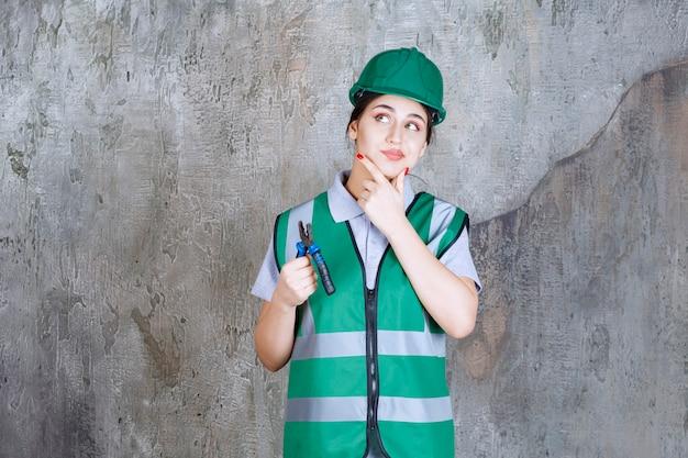 Inżynierka w zielonym kasku trzymająca szczypce do naprawy i wygląda na zdezorientowaną i zamyśloną