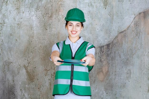 Inżynierka w zielonym mundurze i hełmie trzymająca niebieski folder projektu i oferująca go do weryfikacji