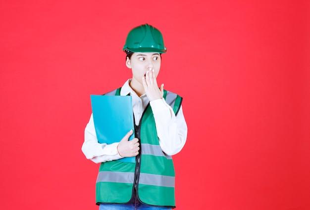 Inżynierka w zielonym mundurze trzyma niebieską teczkę i wygląda na przestraszoną i przerażoną
