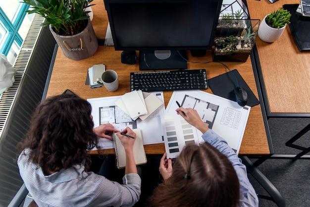 Inżynierki omawiają niektóre projekty i dokonują ostatecznej korekty koloru w biurze. widok z góry.