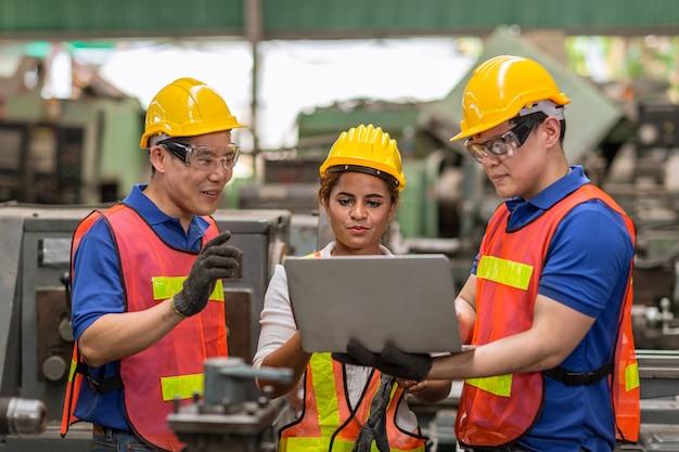 Inżynierki pracujące z męskim zespołem mieszają wyścigi pomagają razem w przemyśle ciężkim z dyskusją o laptopie, dołącz do partnera dobrej pracy zespołowej.