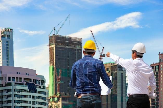 Inżynierowie budowlani pracujący na budowie i zarządzający na placu budowy