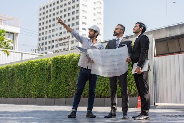Inżynierowie energetyki rozmawiają z dwoma biznesmenami i wskazują na lokalizację instalacji paneli słonecznych na planach budynku