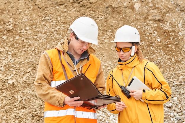 Inżynierowie górnicy omawiają dokumentację roboczą na zewnątrz na terenie kopalni