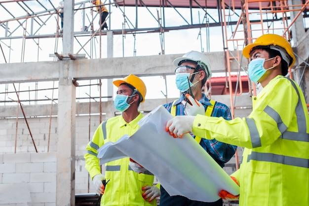 Inżynierowie i pracownicy budowlani noszący maski na twarz w pracy