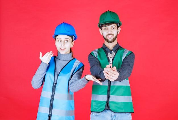 Inżynierowie płci męskiej i żeńskiej trzymający klucz metalowy w kasku.