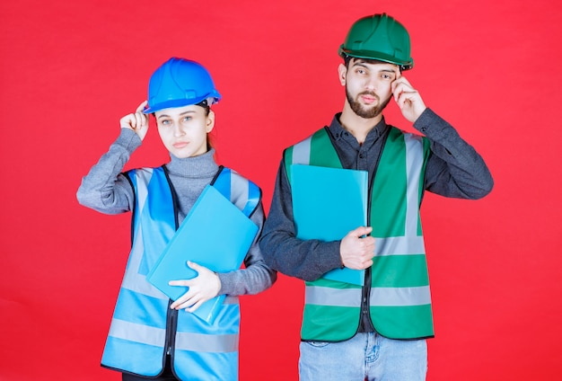 Inżynierowie płci męskiej i żeńskiej w hełmach trzymający niebieskie foldery i wyglądają na zdezorientowanych i zamyślonych.