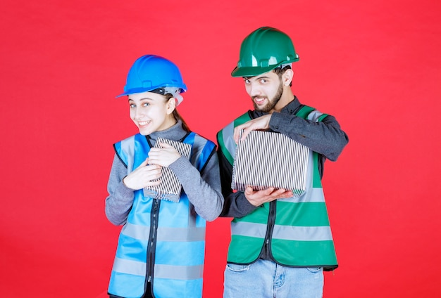 Inżynierowie płci męskiej i żeńskiej w hełmach trzymający srebrne pudełka z prezentami, pozytywnie nastawieni i uśmiechnięci.