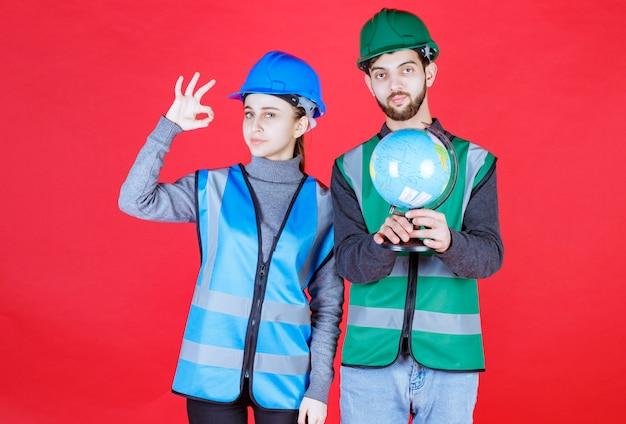 Inżynierowie płci męskiej i żeńskiej w hełmach trzymający światową kulę ziemską i pokazujący pozytywne znaki dłoni.