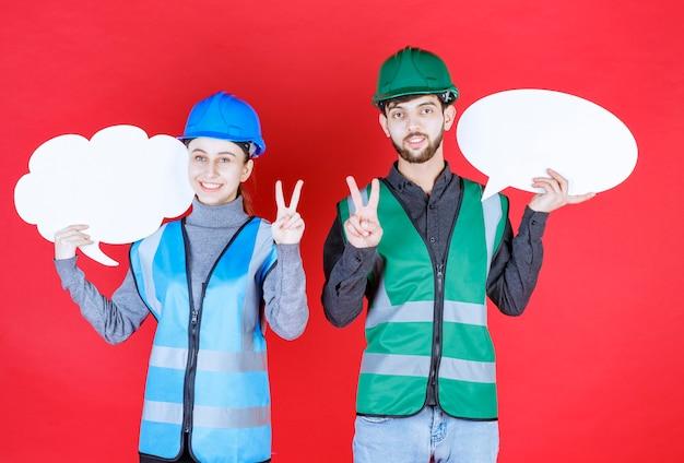 Inżynierowie płci męskiej i żeńskiej w kasku trzymający tablicę informacyjną w kształcie chmury i owalu i pokazujący znak radości.