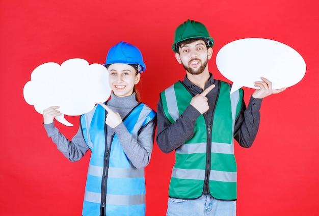 Inżynierowie płci męskiej i żeńskiej w kasku trzymający tablicę informacyjną w kształcie chmury i owalu.