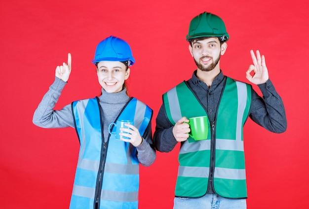Inżynierowie płci męskiej i żeńskiej z hełmem trzymający niebieskie i zielone kubki i pokazujący znak satysfakcji.