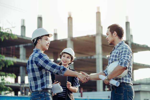 Inżynierowie podają sobie ręce razem z sekretarką z boku.