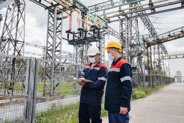 Inżynierowie podstacje elektryczne przeprowadzają przegląd nowoczesnego sprzętu wysokiego napięcia w masce w czasie pandemii. energia. przemysł.