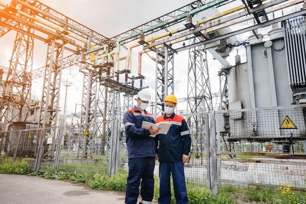 Inżynierowie podstacji elektrycznych przeprowadzają wieczorem przegląd nowoczesnego sprzętu wysokiego napięcia w masce w czasie pandemii. energia. przemysł.